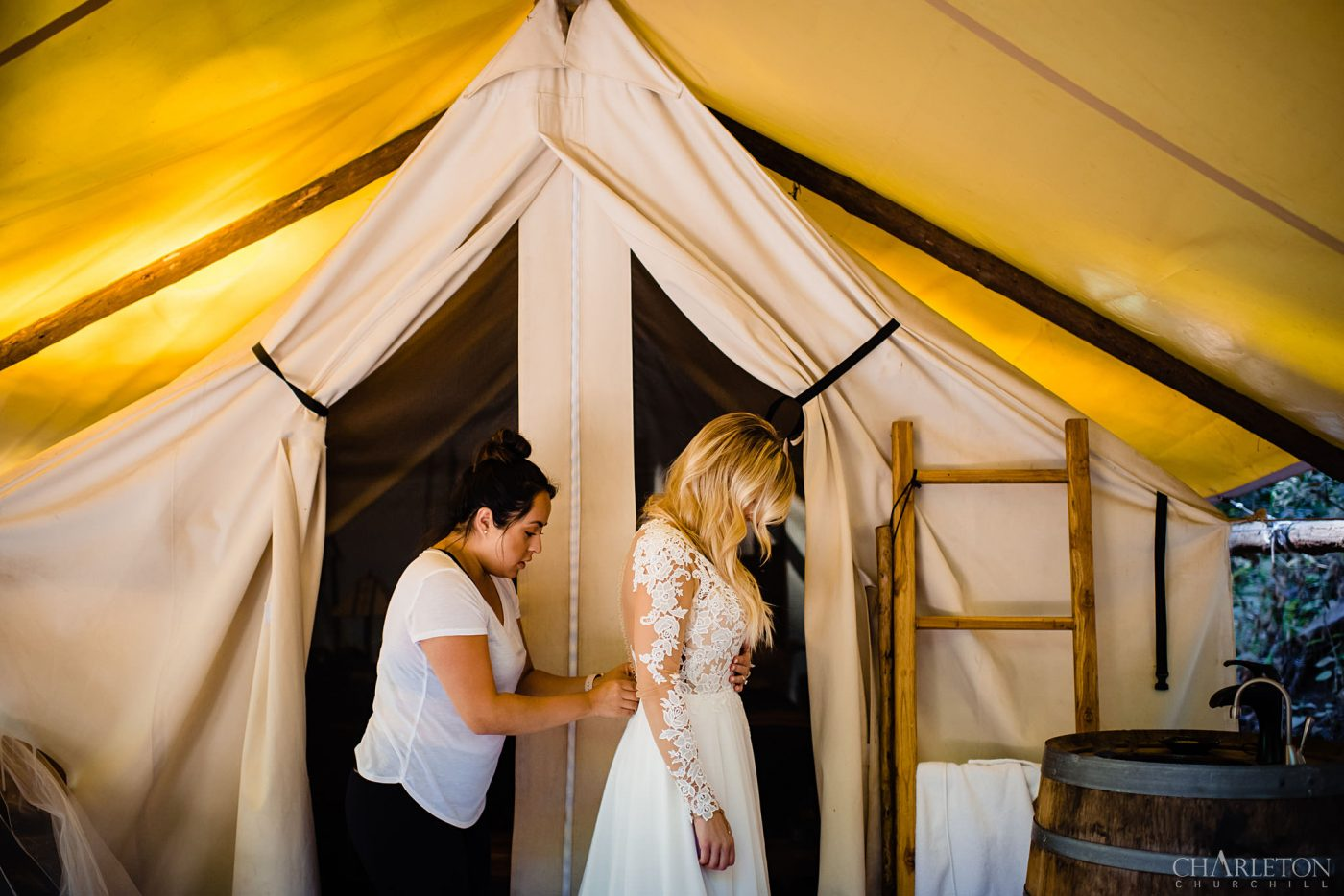 an eloping stylish bride getting wedding gown on at tent of glampgrounds of ventana big sur