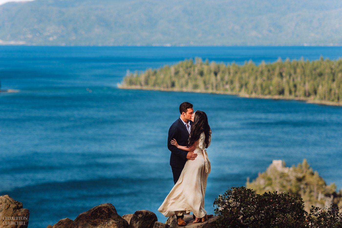beautiful blue lake tahoe with stylish wedding couple kissing on rocks overlooking scenic views of the lake