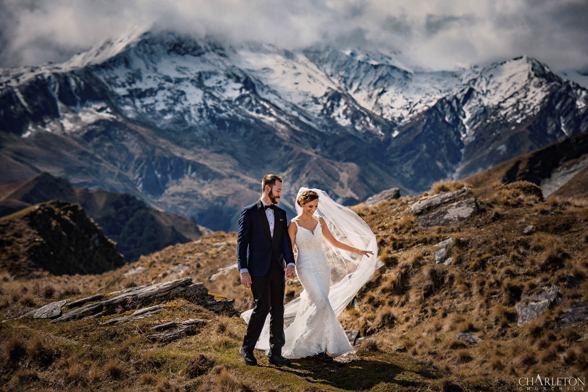 adventure elopement photographer in snow-capped mountains with eloped couple