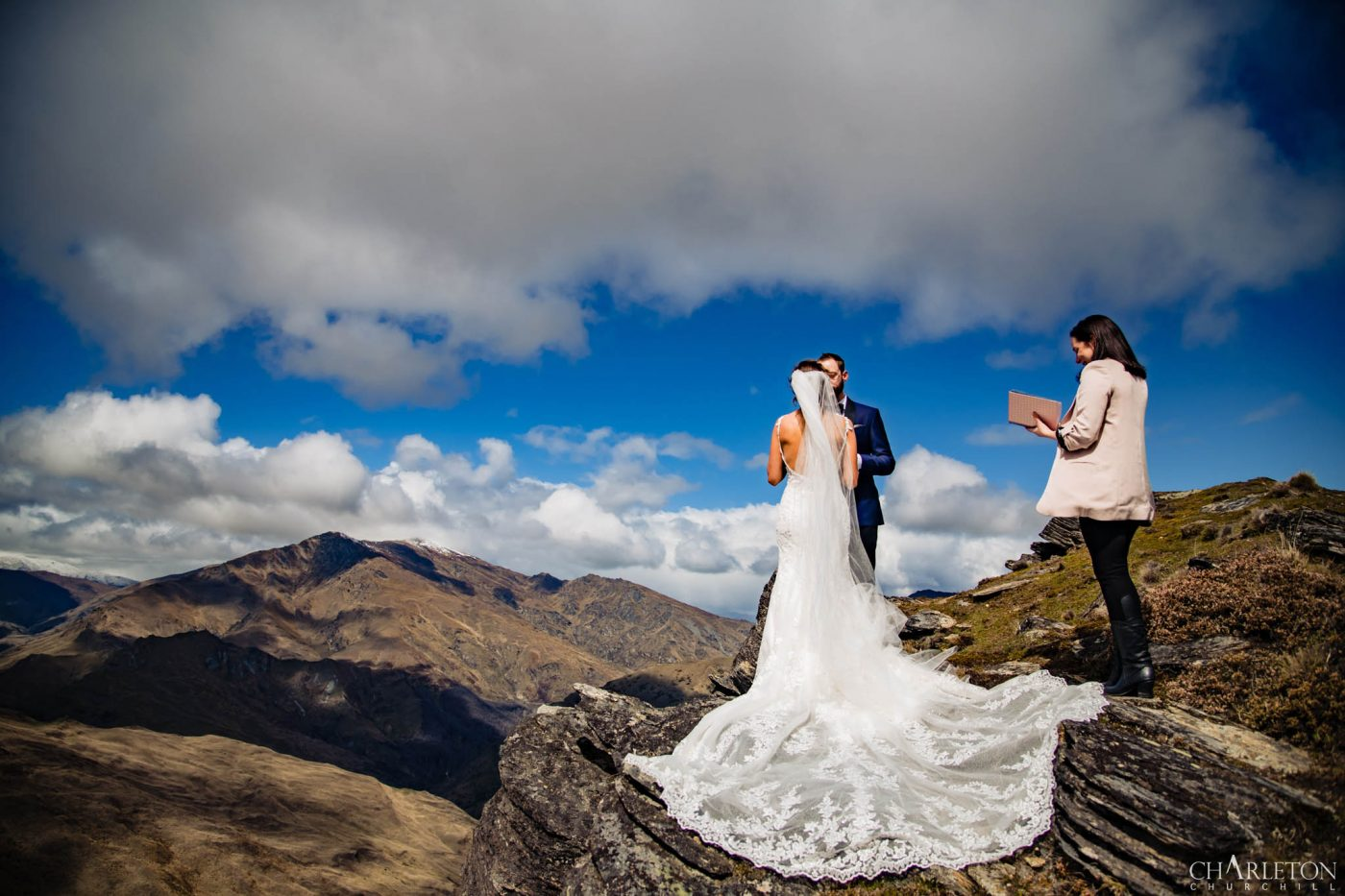 epic elopement on mountain cliff with wedding dress hanging