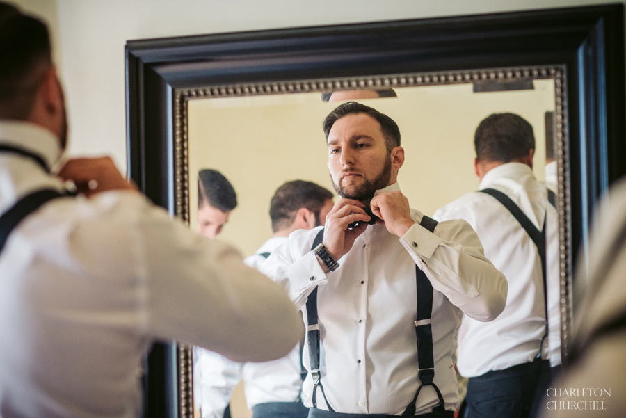 groom getting ready in mirror of villa