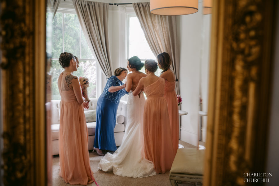 bride putting on her dress with mom and bridesmaids