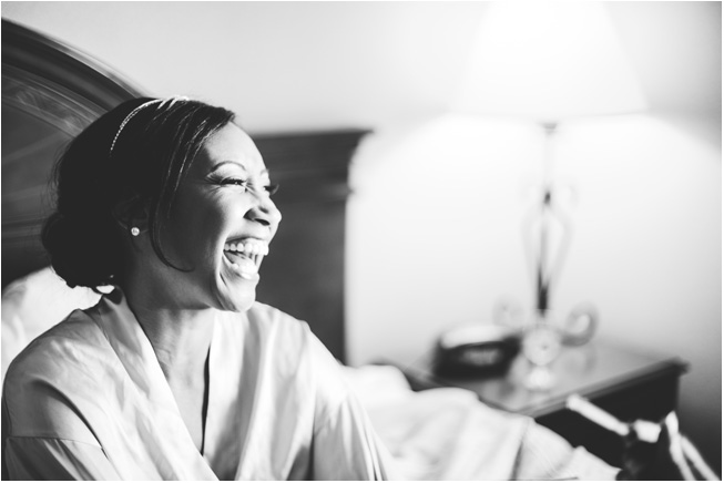 classic black and white photograph of bride before getitng her dress on laughing with joy