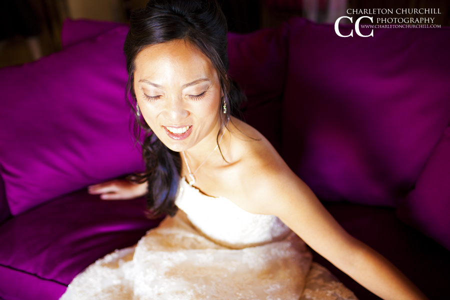 bride laughing on a purple couch in the lodging home for some bridal poses and portraits