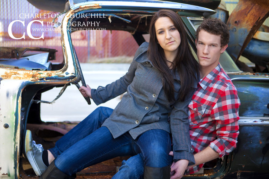 Old rusty car with a lovely couple posing for the camera fashion style