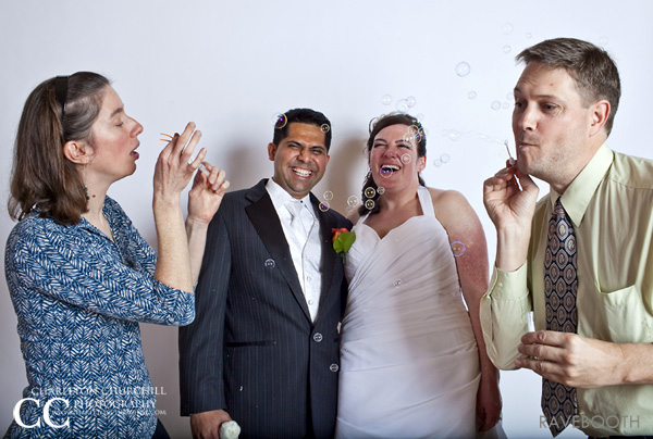 wedding photobooth of couple laughing blowing bubbles