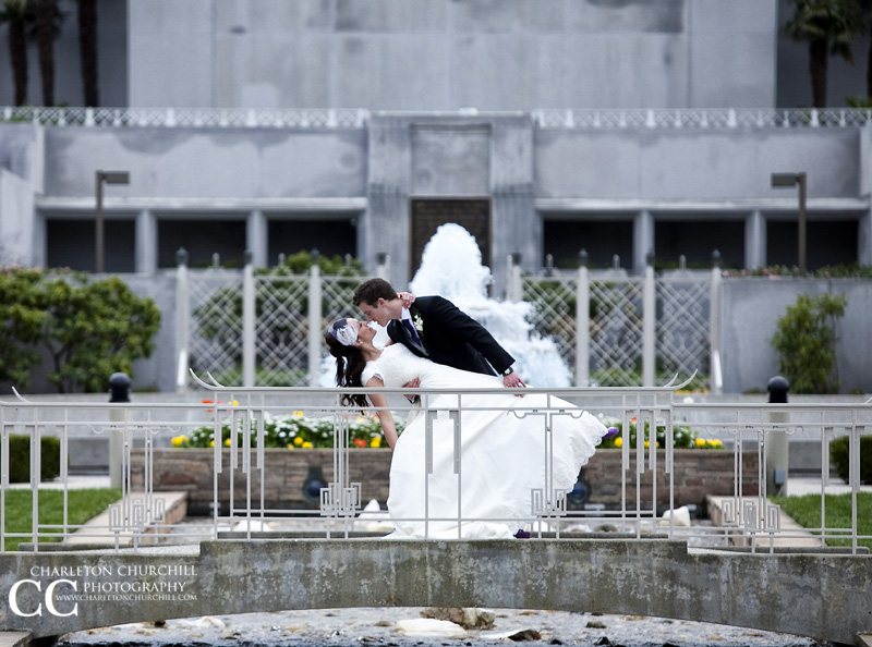 bride and groom in front of LDS Temple in Oakland on the bridge walkway