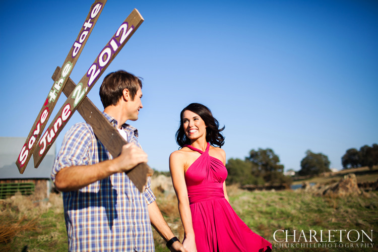 guy and girl holding hands with save the date sign