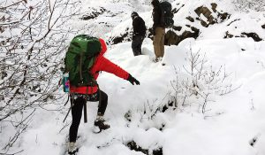 adventure wedding photography couple hiking in the snow with backpacks and low temperatures