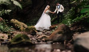 classy woodsy destination wedding photography of couple crossing a stream after a small hike in the forest