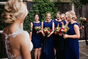 first look of the bridesmaids to the bride with surprised expression and joy