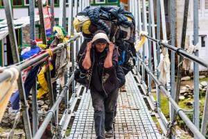 everest sherpa walking across bridge
