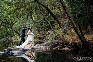 bride and groom walking along arnold forest river
