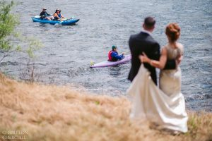 coloma river rafters and kyakers watching bride and groom during photography