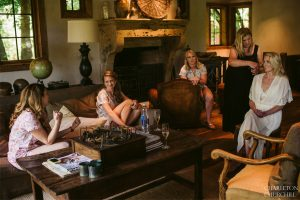 bride and bridesmaids relaxing in living room of anderson ranch luxury wedding venue
