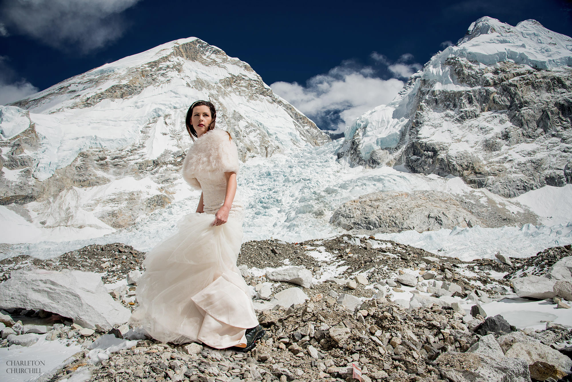 stylish bride at Everest base camp with her wedding dress in front of the khumbu ice-fall