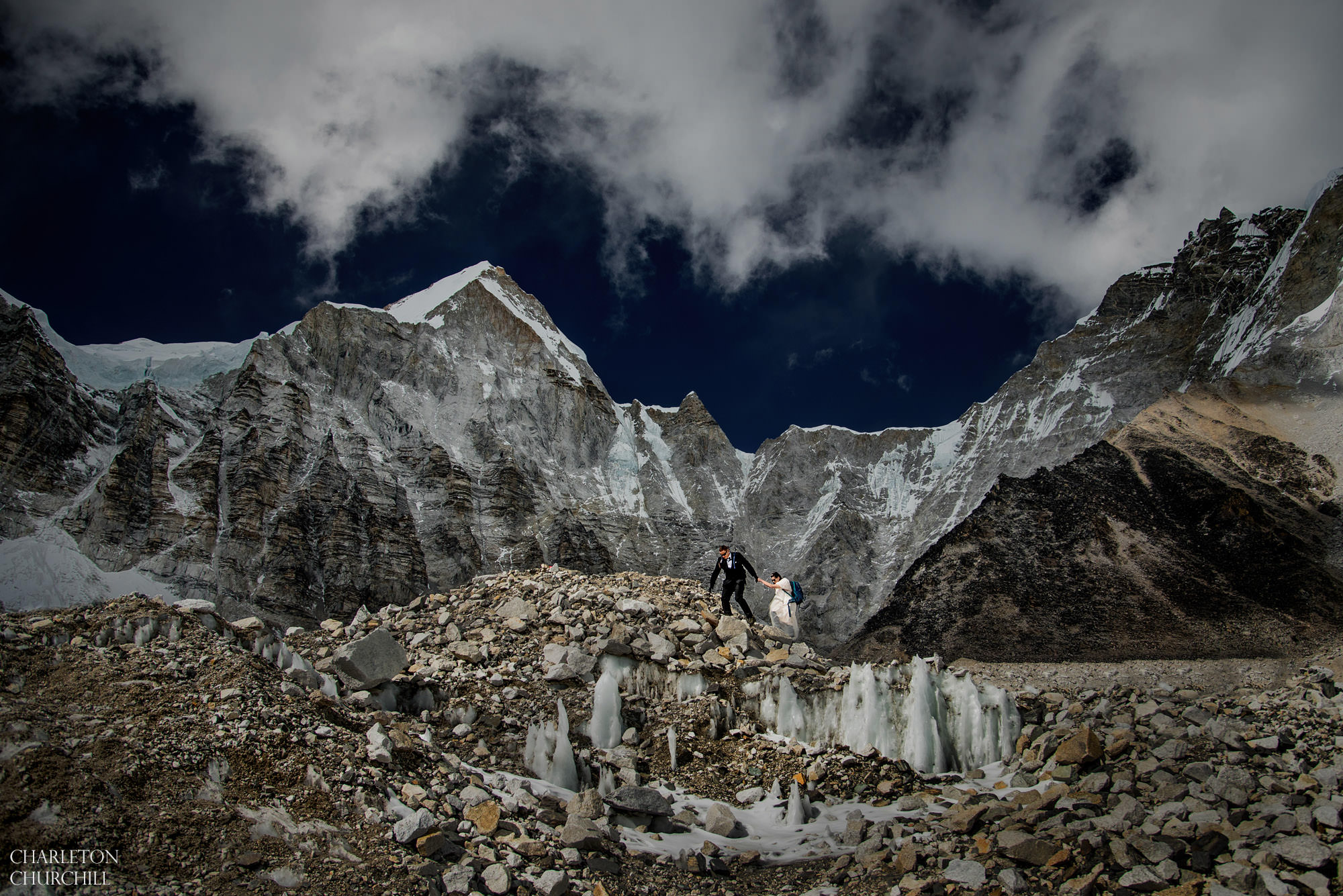 wedding couple hiking in wedding dress and tuxedo on glacier of khumbu of base camp everest trek