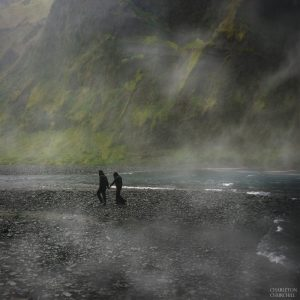 misty waterfalls of skogafoss with engaged couple for photos
