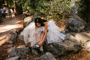 bride tying her shoes on way to mist trail and vernal falls