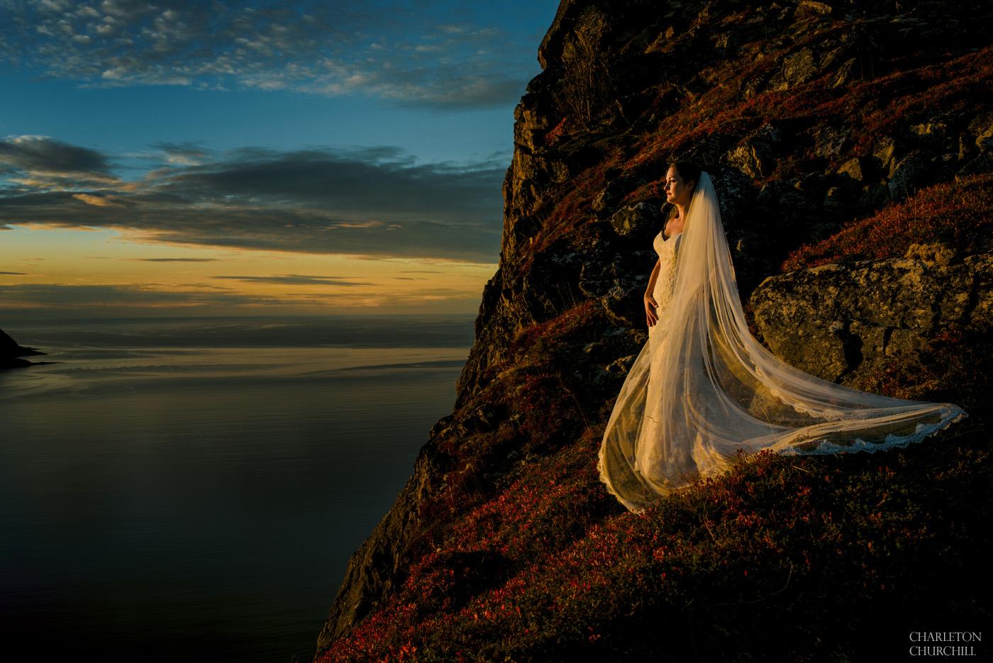 adventure wedding bride on cliff of senja segla mountain range