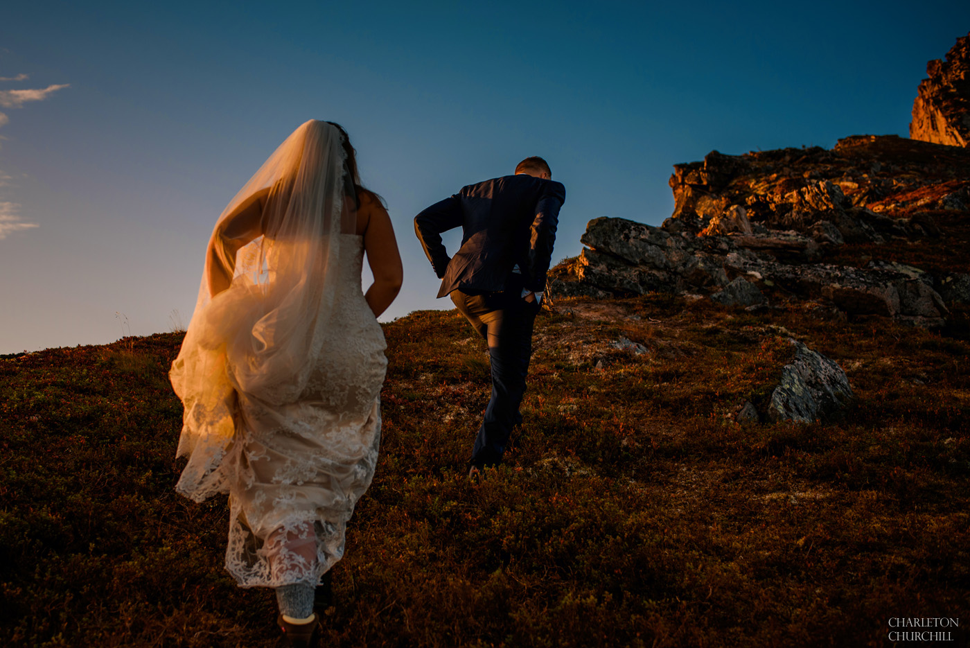hikers in a wedding dress and suit hiking up the mountain
