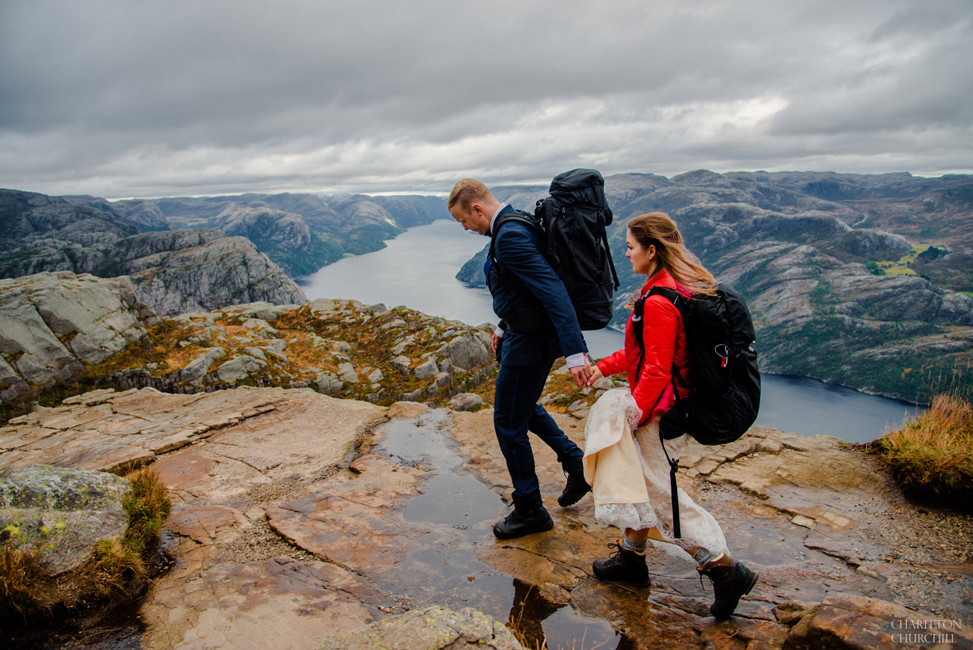 Preikestolen wedding photos in the Lysefjord with adventure couple in backpacks and hiking outfits with a wedding dress and blue suit
