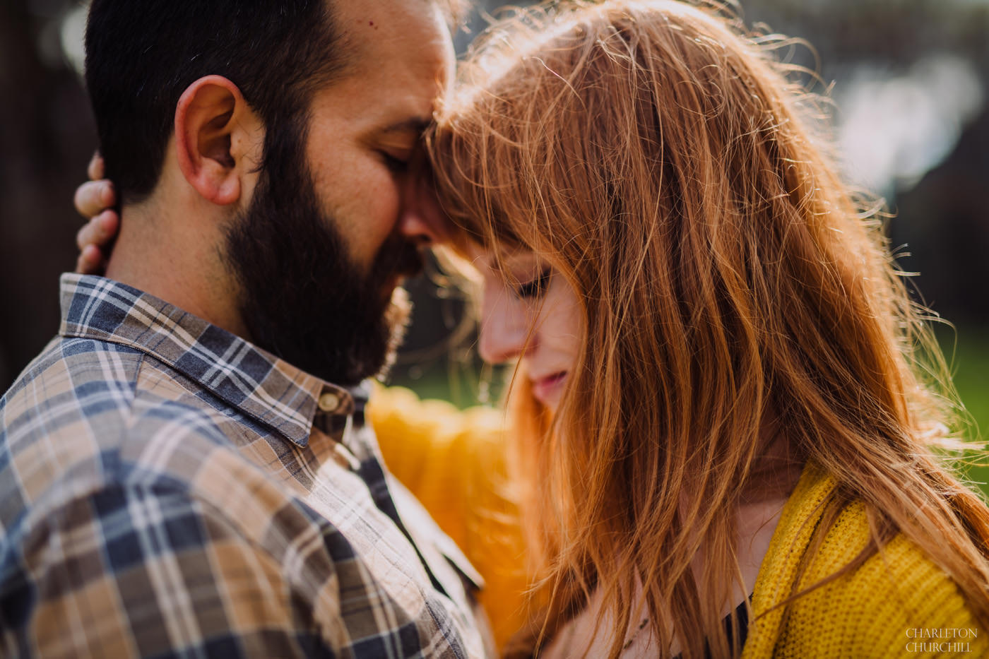moody closeup of engaged couple holding each other romantically