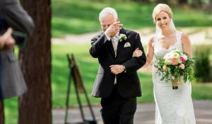 father crying walking down daughter down aisle