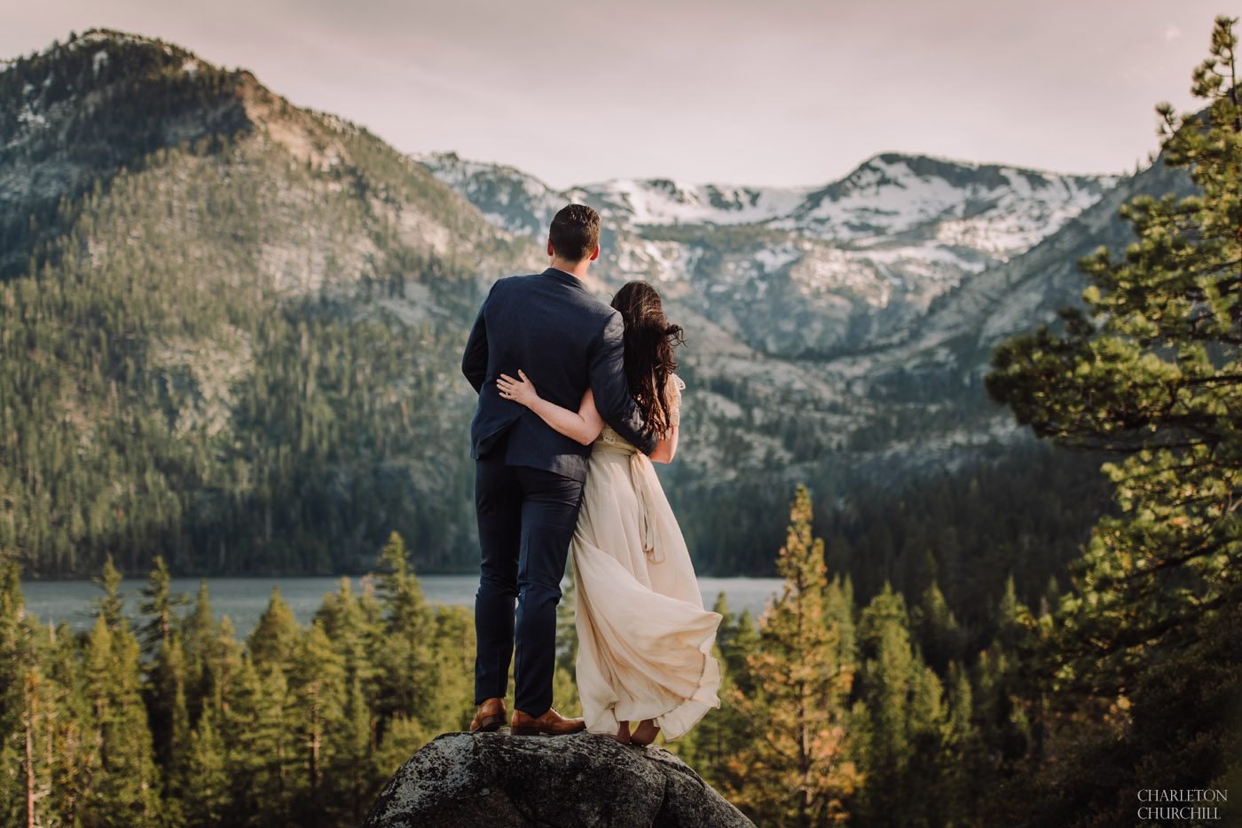epic lake tahoe photo of wedding couple in the wind and the mountains overlooking the majestic beauty of the scenery and views