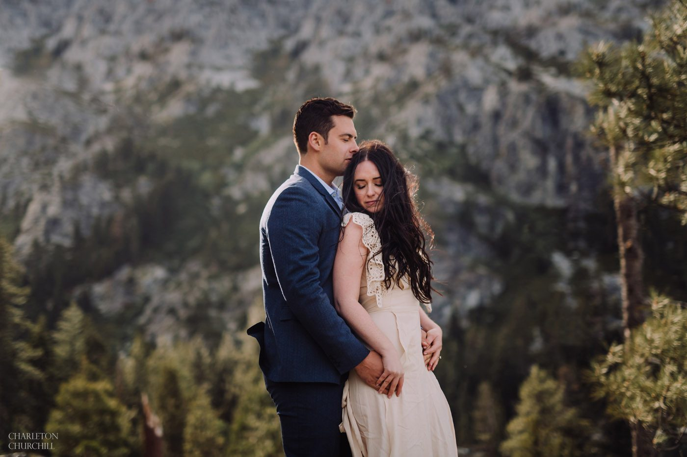 windy engagement session photos around lake tahoe with creme colored dress and blue suit